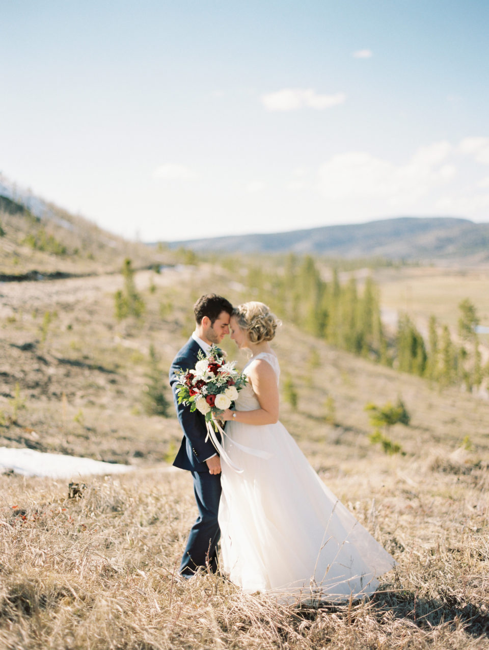 newlyweds with bouquet outdoors mountain