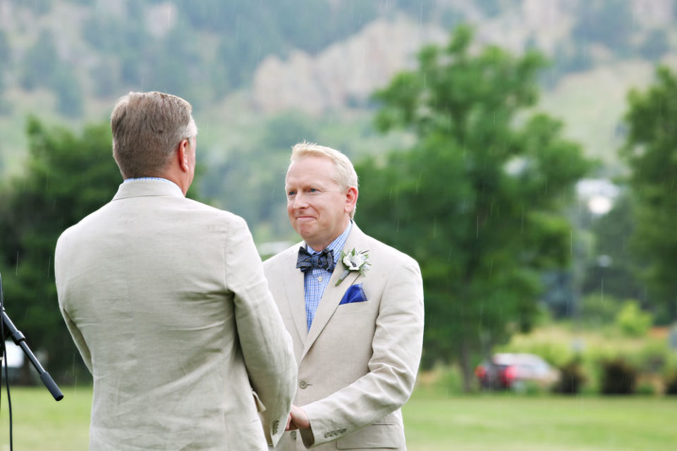 Grooms holding hands trees