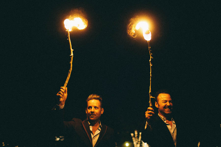 Grooms holding fire smiling