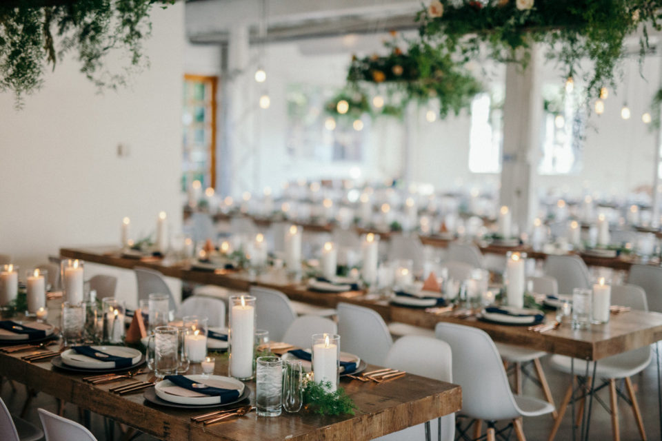 Indoor reception white chairs hanging greenery