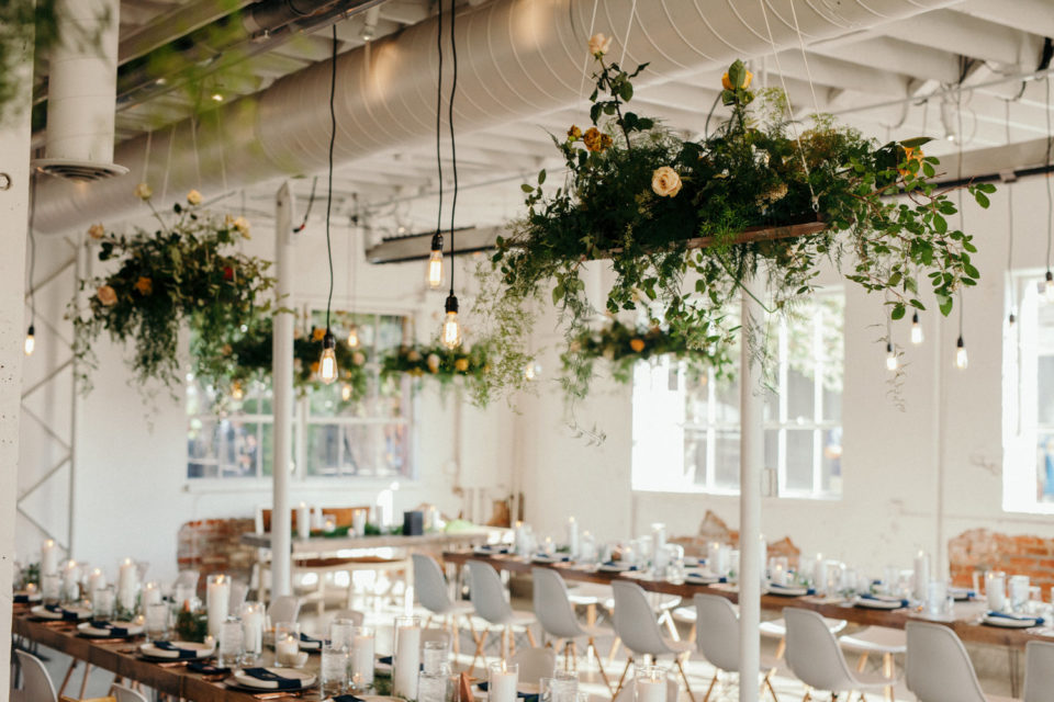 Hanging greenery hanging lights white chairs indoor reception