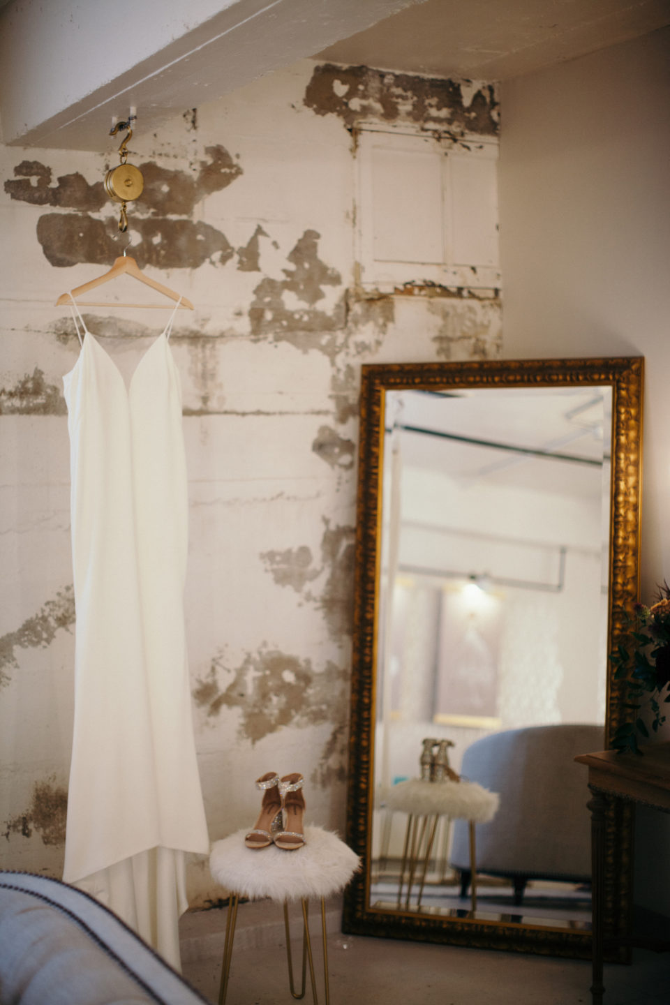 detail shots wedding dress hanging industrial white brick